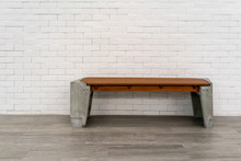 Wooden Chair Or Wood Bench With Concrete Structure Inside A Building Along A Walkway. .