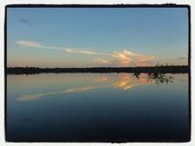 Symmetrical View Of Lake Reflecting Sky At Dusk