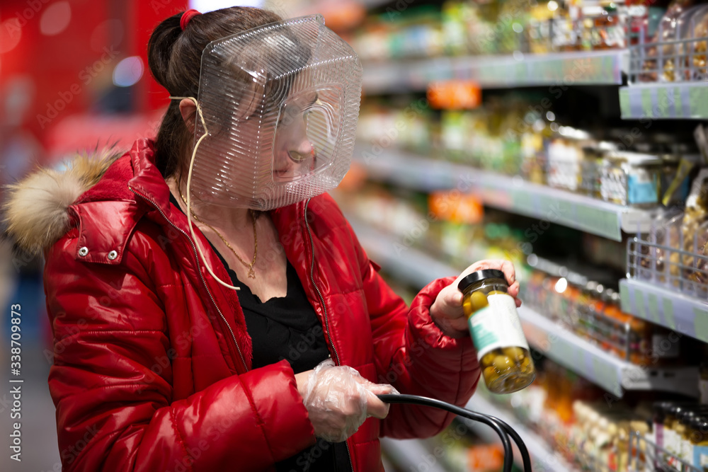 Fototapeta Coronovirus protection. Woman in a store with a plastic box on her face. A funny way to protect against COVID 19.Coronavirus and panic buying concept
