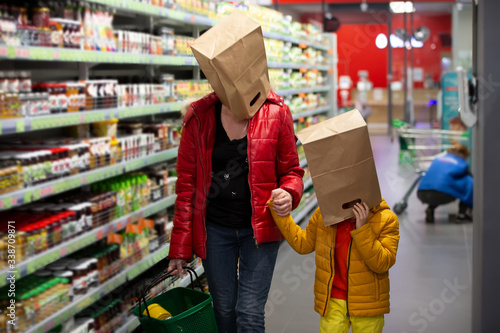 Coronovirus protection. Woman and child in the store with bags on their heads. A fun way to protect against infection 19.Coronavirus and panic buying concept