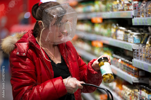 Obraz Coronovirus protection. Woman in a store with a plastic box on her face. A funny way to protect against COVID 19.Coronavirus and panic buying concept - fototapety do salonu