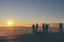 People Standing In Front Of Railing While Sight Seeing Against Clear Sky During Sunset