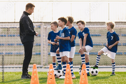 Canvas Print Young coach explaining training rules to children school soccer team