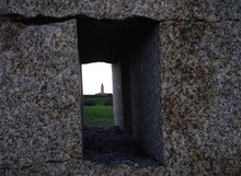 Grassy Area And Building Seen Through Window In Wall