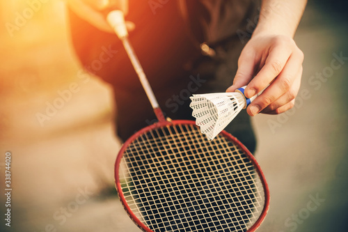 A man in dark clothing is about to throw a white shuttlecock in the air and hit it with a red badminton racket Canvas Print