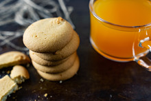 Homemade Shortbread, Round-shaped Pastry On A Dark Old Surface In A Stack Of Crumbs. Next To It Is A Glass Mug With Orange Mulfruit Juice