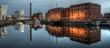 Reflection Of City In Calm River At Dusk