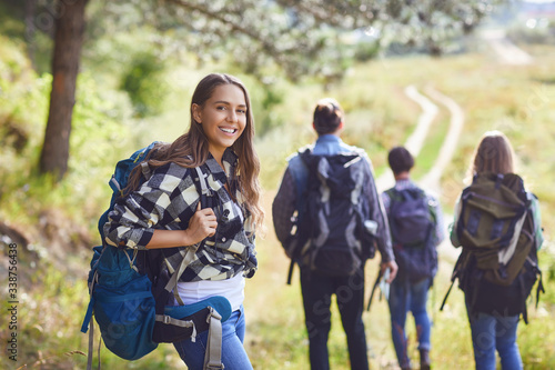 Fototapeta Girl with a backpack with friends, tourists walking in nature. obraz