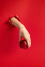 Woman Hand Holding Red Apple Through The Hole In Red Paper