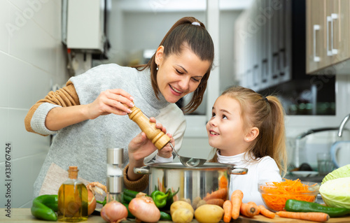 Fototapeta Daughter helping cooking soup and mother add pepper to pan obraz