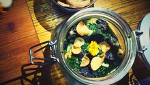 High Angle View Of Escargots With Parsley Salsa In Glass Jar Served On Table