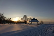 Gazebo On Snow Covered Field Against Sky At Morning