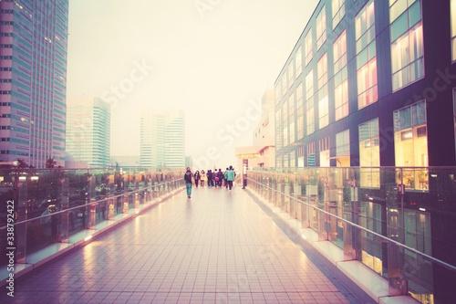Obraz People Walking On Elevated Walkway Amidst City Buildings - fototapety do salonu
