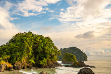 Beautiful View Of A Rocky Caribbean Coast With Dense Tropical Vegetation At Sunset