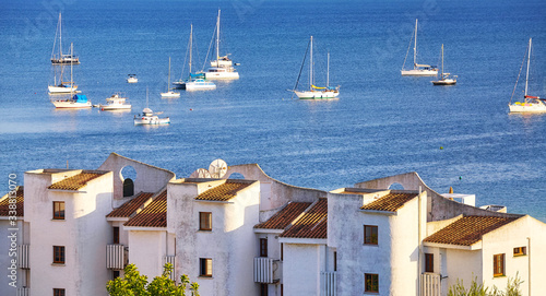 Fotografie, Obraz Port of Alcudia with yachts anchored in the roadstead in distance at sunset, Mallorca, Spain