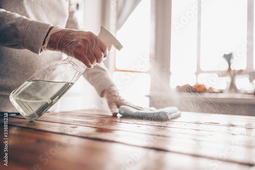 Close up of cleaning home wood table, sanitizing kitchen table surface with disinfectant antibacterial spray bottle, washing surfaces with towel and gloves Slika na platnu