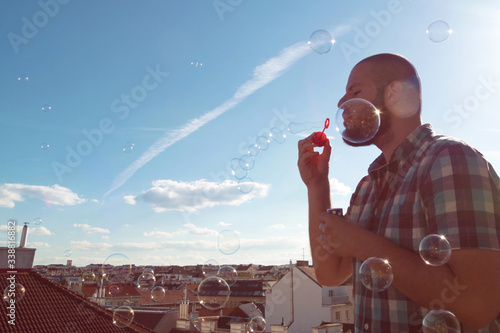 Obraz na plátně Man blowing soap bubbles from his balcony