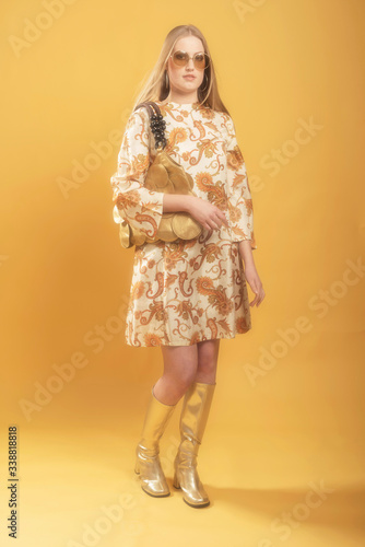 1960s fashion woman in paisley dress and sunglasses holding a handbag Canvas Print