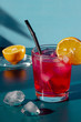 pink cocktail on a blue background with lemon