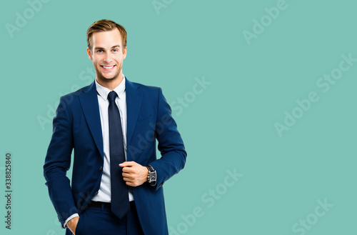 Portrait of happy confident businessman in blue suit and tie, isolated over green marine color background Fototapeta