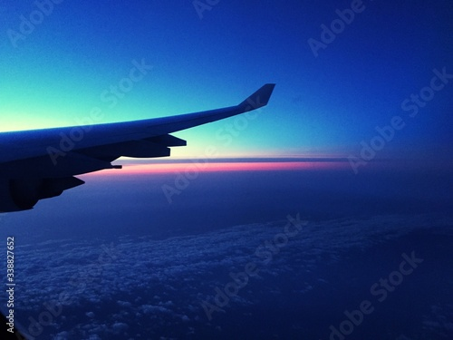 Fotografiet Cropped Image Of Airplane Wing Over Landscape At Dusk