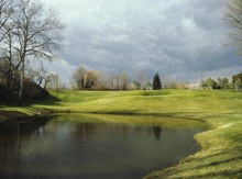 Pond In Golf Course Against Cloudy Sky