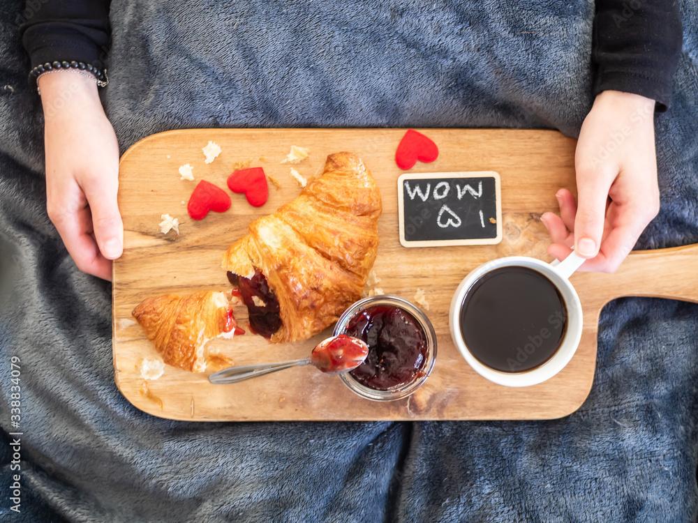 Fototapeta Frau mit einem Serbiertablett mit frischen Croissant, eine Tasse Kaffee und Erdbeerkonfitüre auf einer grauen Decke, Muttertag, Frühstück, soziale Distanz