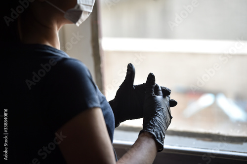 Fototapety, obrazy: Indoors photo with unrecognizable person wearing black latex medical gloves in times of coronavirus pandemic