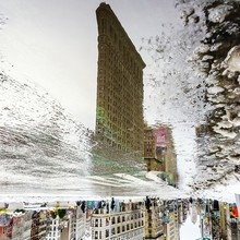 Reflection Of Flatiron Building In Puddle