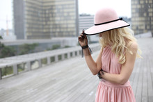Blonde In Pink Hat And Pink Dress Stands On Street Of Paris. Faceless Girl In Pink Hat