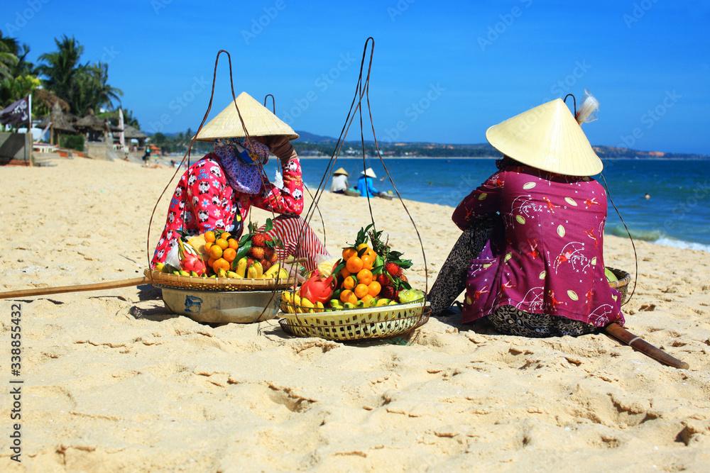 Fototapeta wietnamskie kobiety w tradycyjnych kapeluszach siedzące na plaży