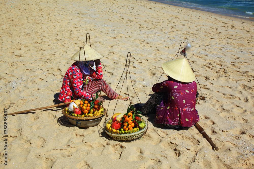 Fototapeta wietnamskie kobiety w tradycyjnych kapeluszach sprzedające owoce na plaży