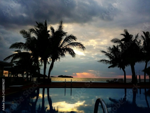 Silhouette Palm Trees By Swimming Pool At Beachside Resort During Sunset Fototapeta