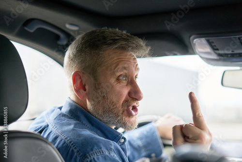 Photo unfriendly aggressive car driver showing the middle finger