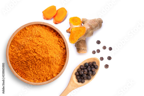 Curcumin powder ( tumeric ground, turmeric, Curcuma ) in wooden bowl and black peppercorns in spoon isolated on white background Canvas Print