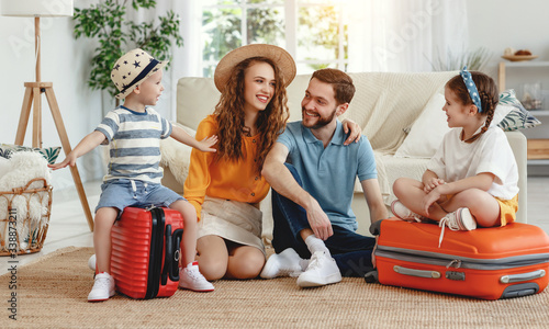 Obraz Cheerful family with suitcases on floor - fototapety do salonu