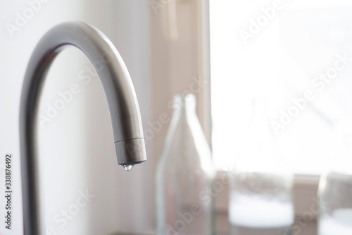 Drop of water hanging from a faucet in the kitchen at home Tablou Canvas