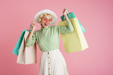 Spring Shopping Concept: Happy Smiling Fashionable Woman Wearing Trendy Clothes Posing With Colorful Paper Bags. Pink Background. Copy, Empty Space For Text