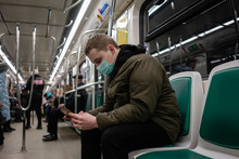 Young Man In Commuter Train, Wearing Face Mask, Using Smartphone
