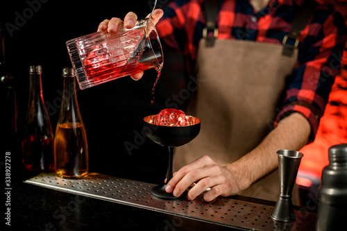 Male bartender accurate pours red campari drink from mixing cup to wineglass Canvas Print