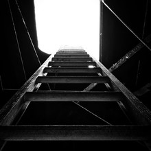 Symmetrical Upward View Of Ladder In Cellar Sky In Background