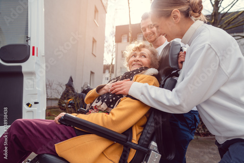 Photo Senior woman in wheelchair being picked up by transport service