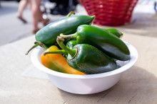 Anaheim Or Chili Peppers In A White Bowl On A Table At A Farmer's Market. The Small Hot Green Peppers Have Thick Rich Green Skins With Long Stalks. There's One Orange Pepper Turning Green.