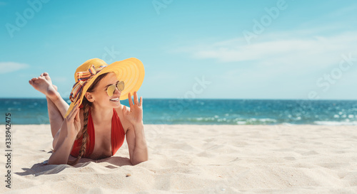 Tablou Canvas Woman enjoying her vacation by the sea tanning in the beach sand
