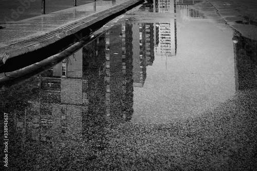 Photo Reflection Of Buildings In Puddle On Road