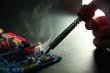 backdrop of smoking soldering iron on dark background