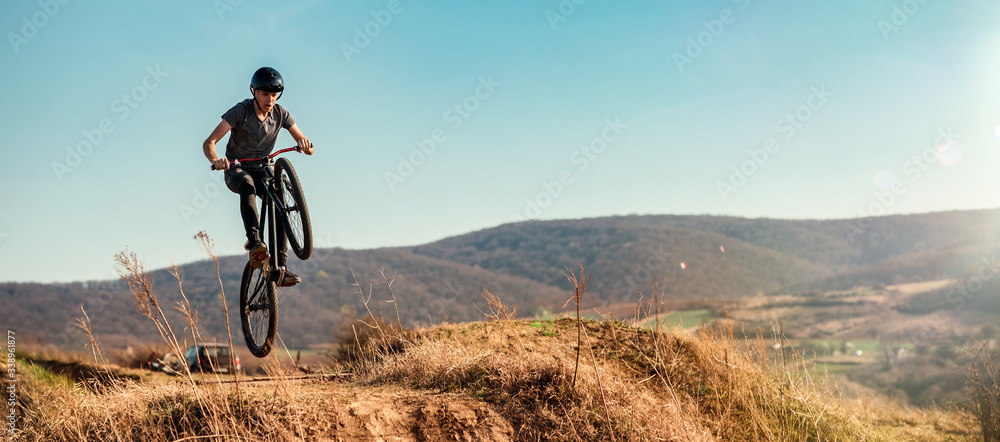 Fototapeta Dirt bike rider jumping in bike park on mountain bike