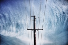 Low Angle View Of Telephone Pole Against Cloudy Sky