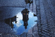 Reflection Of Westerkerk Church In Puddle On Street