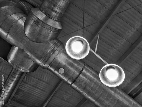 Low Angle View Of Illuminated Pedant Lights And Pipeline In Factory Fototapet